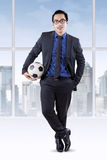 Male businessperson with football in office Stock Images