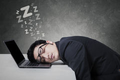 Male businessperson sleeping on laptop Stock Photos