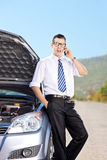 Male businessperson talking on phone on an open road Royalty Free Stock Image