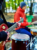 Male buskers on autumn outdoor play guitar. Royalty Free Stock Photo