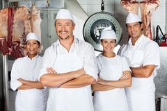 Male Butcher With Confident Team. Portrait of mature male butcher with confident team in butchery Royalty Free Stock Photo