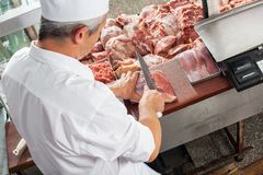 Male Butcher Cutting Meat At Display Cabinet Stock Image