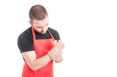 Male butcher having wrist pain Stock Image