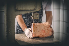Male butcher`s hand slicing meat Royalty Free Stock Photography