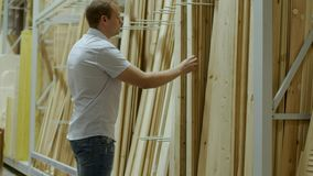 Male buyer chooses wooden boards in shop of building materials. Hardware store, racks, shop of building materials and tools, male buyer chooses the instruments stock footage