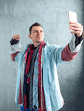 Male buyer makes selfie at clothing store. Male buyer dressed in many clothes makes selfie on phone camera at the clothing store. Shopping concept Royalty Free Stock Images