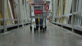 Male buyer with shopping cart walks in the store. Male customer with shopping cart walks in the hardware store, racks, shop of building materials and tools, male stock video footage
