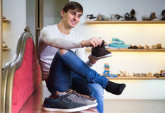 Male buying summer shoes. Smiling male buying summer shoes in a shoe store Stock Photography