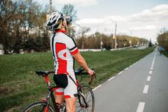 Male bycyclist drinks water while training. Male bycyclist in helmet and sportswear drinks water while training. Workout on bike path, cycling on asphalt road Stock Image