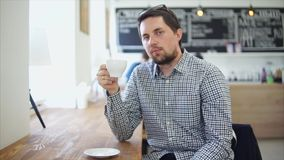 Male cafe visitor enjoying cup of coffee. He holding it stock video footage