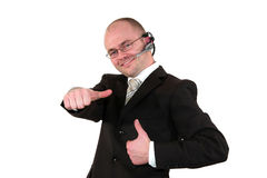 Male call center agent posing with thumbs up. A smiling male call center agent with glasses and a headset posing with the thumbs up sign, isolated on white Royalty Free Stock Photography