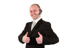 Male call center agent posing with thumbs up. A smiling male call center agent with  a headset posing with the thumbs up sign, isolated on white background Stock Image