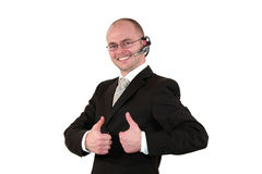 Male call center agent posing with thumbs up. A smiling male call center agent with glasses and a headset posing with the thumbs up sign, isolated on white Stock Image