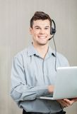 Male Call Center Employee With Laptop Stock Photo