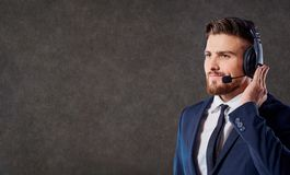 A male call center operator with headset. A male call center operator with headset on his head answers calls on the office background Stock Photos