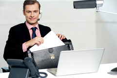 Male call centre executive arranging paper works Stock Photography