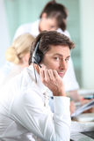 Male call centre worker. Dealing with customer Stock Photos