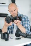 Male camera technician assembling cam. Male camera technician assembling the cam Royalty Free Stock Images