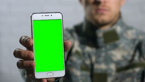 Male in camouflage showing smartphone with green screen closeup, application. Stock footage stock footage