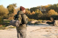 Male camper with backpack and sleeping bag in wilderness. Space for text stock photos