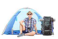 Male camper sitting in front of a blue tent Stock Image