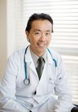 Male Cancer Specialist Sitting In Hospital. Portrait of Asian male cancer specialist with stethoscope around neck sitting in hospital Stock Photography