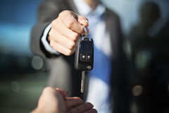 Male car dealer dressed in a suit giving car keys to a female person, focus on hands Stock Photo