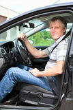 Male in car with ignition key in hand. Happy mature man with car key sitting in own land vehicle Royalty Free Stock Photo