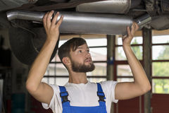 Male car mechanic changing car exhaust Royalty Free Stock Photos