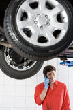 Male car mechanic, in red overalls and protective gloves, using mobile phone near hydraulic platform in auto repair shop, smiling Royalty Free Stock Photos