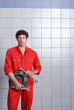 Male car mechanic, in red overalls, standing in auto repair shop near tiled wall, holding vehicle part and wrenches, smiling, port Royalty Free Stock Images