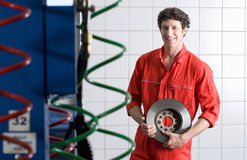 Male car mechanic, in red overalls, standing in commercial garage, holding vehicle part, smiling, portrait Royalty Free Stock Photography