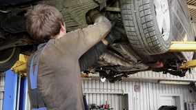 Male car mechanic with spanner working under automobile in garage. Male car mechanic with spanner tool working under automobile in garage stock footage