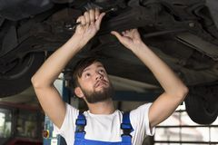 Male car mechanic working under car Royalty Free Stock Photos