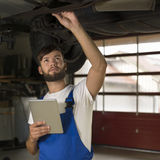 Male car mechanic working under car with tablet PC Stock Photo