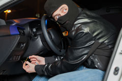 Male car thief breaks the ignition switch. Carjacker with balaclava on his head hack car. Carjacking danger concept. Auto transport crime. Vehicle insurance Stock Photo