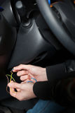 Male car thief breaks the ignition switch. Carjacker with balaclava on his head hack car. Carjacking danger concept. Auto transport crime. Vehicle insurance Stock Image