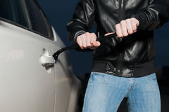 Male car thief open door with jemmy. Male car thief hands trying to open door with jemmy. Carjacker unlock vehicle with crowbar on parking. Carjacking danger Stock Photography