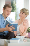 Male caregiver assisting senior woman stock photo