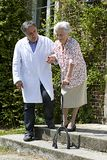 Male caregiver helping senior patient with a walking stick Royalty Free Stock Photography