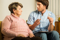 Male carer supporting old woman. Photo of professional male carer supporting sick old woman Royalty Free Stock Image
