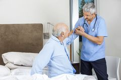 Male Caretaker Assisting Senior Man Stock Photography