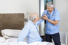 Male Caretaker Assisting Senior Man. Male caretaker assisting senior men to get up from bed at nursing home stock photography