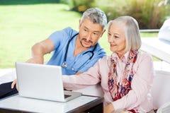 Male Caretaker Assisting Senior Woman In Using Royalty Free Stock Image