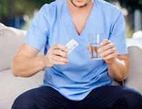 Male Caretaker Holding Blister Pack And Glass Of Stock Photography