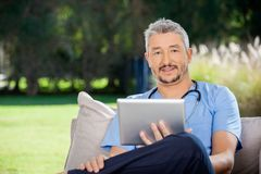 Male Caretaker Holding Tablet Computer. Portrait of male caretaker holding tablet computer while sitting at nursing home porch royalty free stock photography