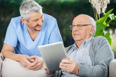 Male Caretaker Looking At Senior Man Using Tablet Royalty Free Stock Images