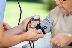 Male Caretaker Measuring Blood Pressure Of Elderly. Cropped image of male caretaker measuring blood pressure of elderly men at nursing home Royalty Free Stock Photography
