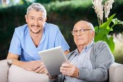 Male Caretaker And Senior Man Holding Digital. Portrait of smiling male caretaker and senior men holding digital tablet at nursing home porch stock images