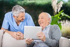 Male Caretaker And Senior Man Laughing While Using Royalty Free Stock Image